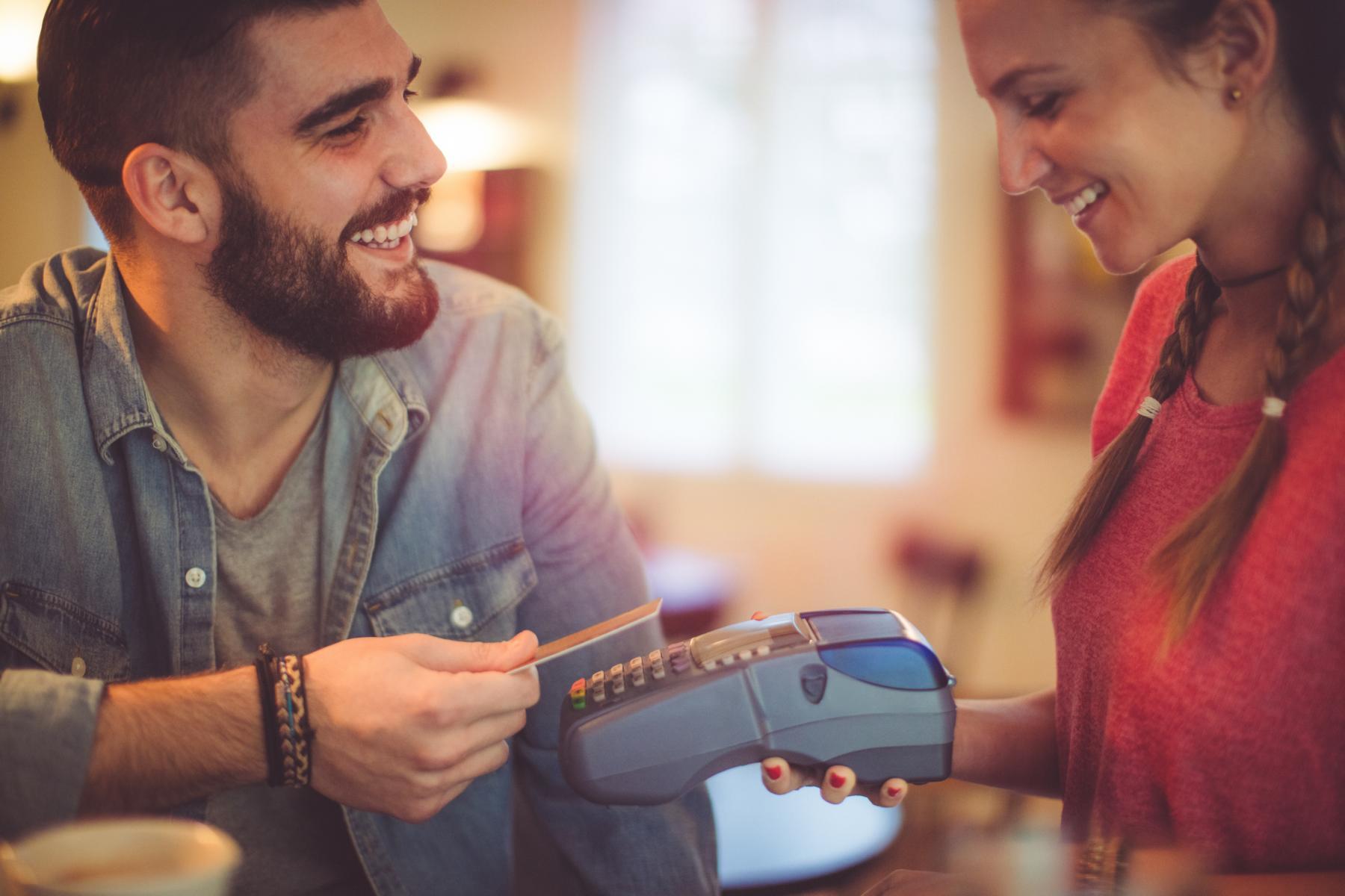 Kontaktlos Bezahlen. Mann bezahlt kontaktlos mit seiner Kreditkarte